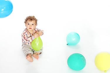 un petit mec assis sur un fond blanc avec dans les mains un ballon de baudruche vert, photographiée par notre photographe Rachel Joubi