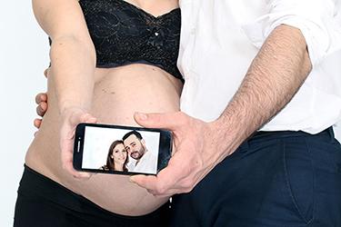 grossesse heureuse photographiée par notre photographe Rachel Joubi, couple montrant leur portrait sur un smart phone qui est placé devant le ventre bombé de la futur maman.