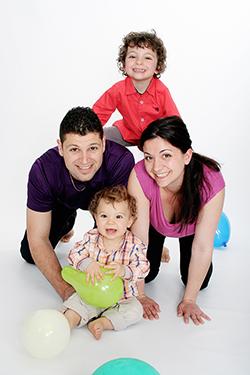 couple avec deux enfants posant au sol dans le studio de notre photographe Rachel Joubi