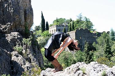 Jolie femme se cambrant en arrière photographiée par notre photographe Rachel Joubi en extérieur, nous apercevons derriere la jeune femme un château