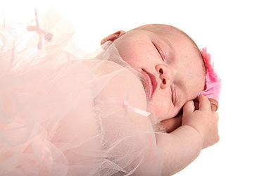 bébé qui fait un joli dodo sur fond blanc avec un petit noeud rose sur la tête photographié par notre photographe Rachel Joubi