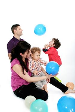 famille heureuse photographiée par notre photographe Rachel Joubi dans un moment de jeu avec des ballons de baudruches.