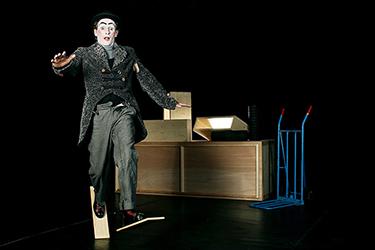 Clown en action sur scène, en train de marcher avec des planches de bois fixés au pieds, photographié par notre photographe Rachel Joubi