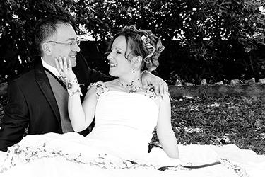 jeunes mariés assis dans l'herbe se regardant amoureusement photographiés en noir et blanc par notre photographe Rachel Joubi
