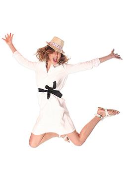 jeune femme avec un chapeau heureuse, qui saute sur un fond blanc en studio photographiée par notre photographe Rachel Joubi