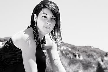 Joli portrait en noir et blanc d'une jeune femme photographiée par notre photographe Rachel Joubi en extérieur, nous apercevons derriere la jeune femme des montagnes