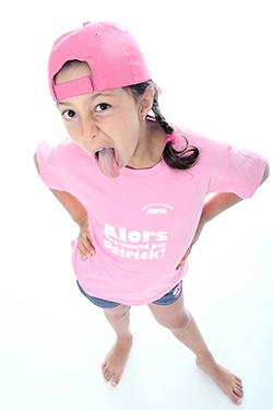 jeune fille avec une casquette tirant la langue en grimaçant avec les mains placées sur les hanches photographiée par notre photographe Rachel Joubi