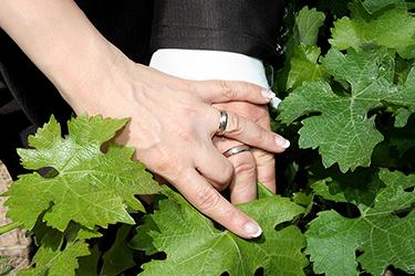 les mains des jeunes mariés avec leur bagues toutes neuves posées sur des feuilles de vigne photographiées par notre photographe Rachel Joubi