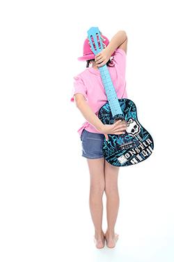 jeune fille de dos en plein-pied qui tient une guitare bleue photographiée par notre photographe Rachel Joubi