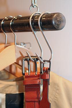 détail d'un portique pour vêtements montrant des boucles de ceinture, photographiées par notre photographe Rachel Joubi