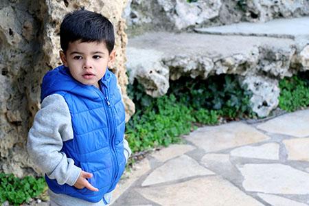 enfant pris en photo à l'extérieur avec un blouson bleu, shooting de Rachel Joubi