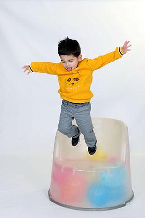 mec en train de sauter d'un fauteuil transparent dans lequel se trouvent des ballons colorés, petit mec qui s'est régalé pendant le shooting de Rachel Joubi