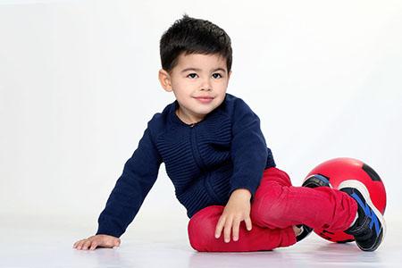 enfant posant en studio avec un pantalon rouge et son pull bleu-marine. Shooting de Rachel Joubi