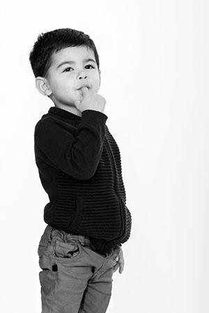 photo en noir et blanc, petit mec avec un doigt dans la bouche en plan américain