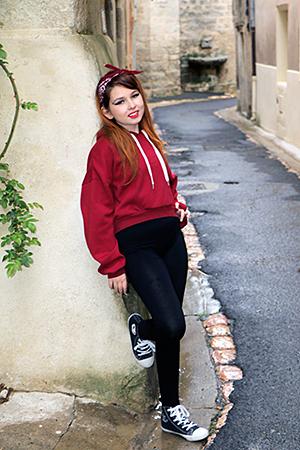 Gayaan dans une petite rue de village pose pour une photo fashion, tenue sportive avec un haut rouge ample et un legging noir et tennis Disney Mr Jack Photographiée par Rachel Joubi d'Occitanie