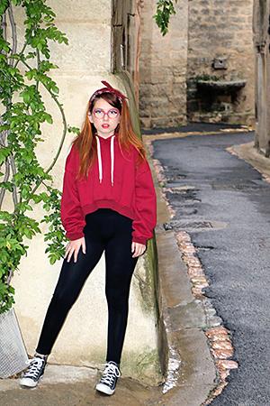 Gayaan pose en extérieur pour une photo mode, tenue sportive avec un haut rouge ample et un legging noir et tennis Disney Mr Jack Photographiée par Rachel Joubi d'Occitanie