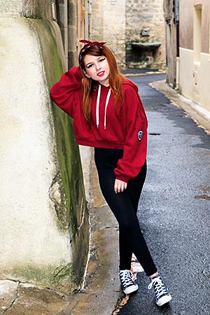 Gayaan dans une petite rue de village pose avec Style habillée en tenue sportive avec un haut rouge ample, un legging noir et des tennis Disney Mr Jack, Photographiée par notre photographe Rachel Joubi d'Occitanie