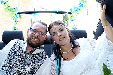 Les mariés dans la voiture posant avec un joli sourire.