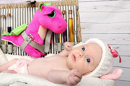 Un beau bébé dans une petite mallette avec son doudou Dino, photographié par Rachel Joubi