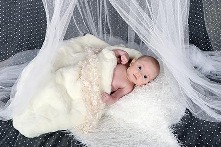 Bébé photographié sur un coussin blanc par Rachel Joubi
