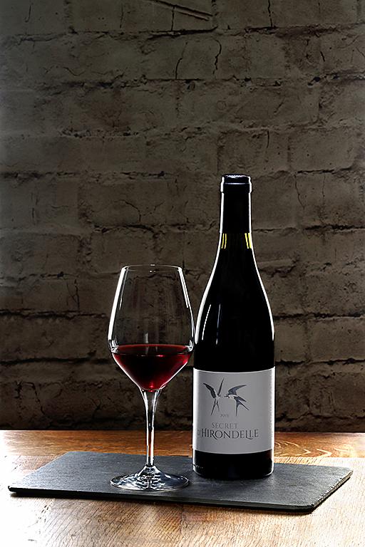 bouteille de vin avec son verre rempli shootés en studio sur un socle en ardoise qui est lui-même posé sur une table en bois. Photographiés par notre photographe Rachel Joubi