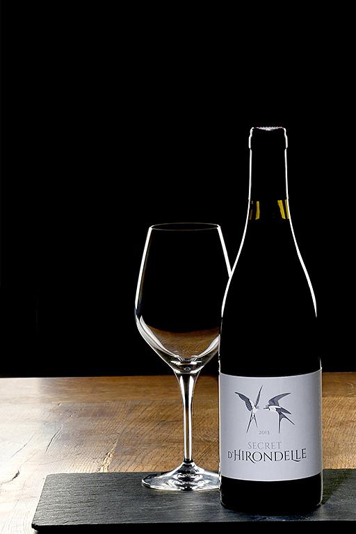 bouteille de vin avec son verre vide shootés en studio sur un socle en ardoise qui est lui-même posé sur une table en bois. Photographiés par notre photographe Rachel Joubi