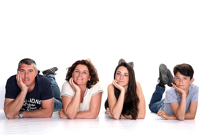 petite pose d'une famille avec deux enfants au sol dans un studio pour notre photographe Rachel Joubi