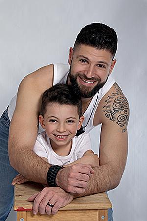 portrait d'un super papa avec un de ses fils accoudés sur un tabouret en bois pour notre photographe Rachel Joubi