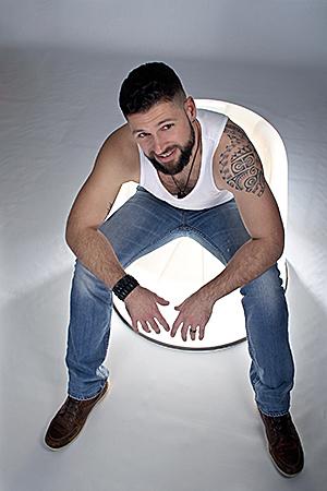 homme assis sur un fauteuil lumineux tatoué à l'épaule gauche photographié par Rachel Joubi