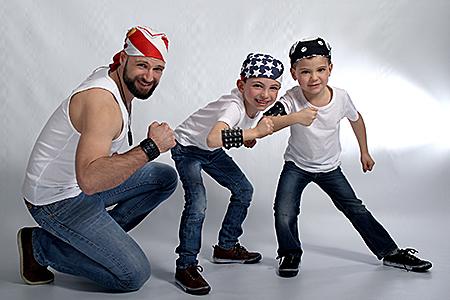 un super papa avec ses deux fils qui font une démonstration de force en contactant leur biceps, photographiés par Rachel Joubi